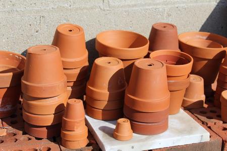 ollas de barro: diferentes tama�os de ollas de barro terracota en ladrillos al aire libre