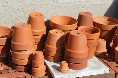 different sizes of terracotta clay pots on bricks outdoors Stock Photo