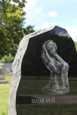 Gravestone with bible verse and small child cupped safely in a large hand
