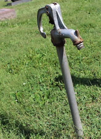 Rusty Water well spicket in a graveyard