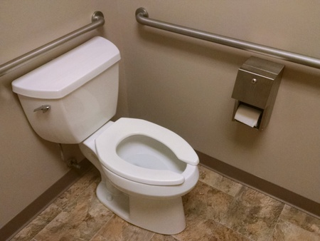 The corner of a public restroom with a wheelchair accessible toilet. Stock Photo