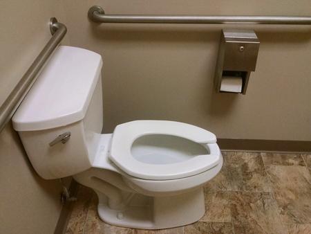 paraplegico: La esquina de un baño público con un aseo accesible en silla de ruedas. Foto de archivo
