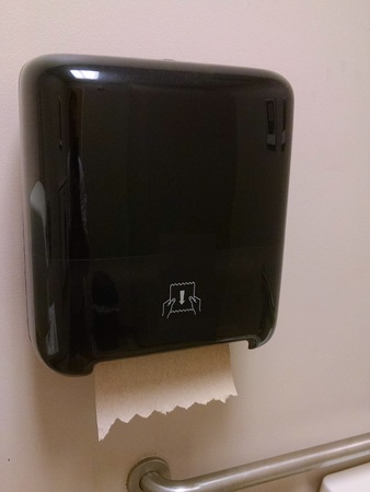 Black Paper towel dispenser on the wall in the bathroom