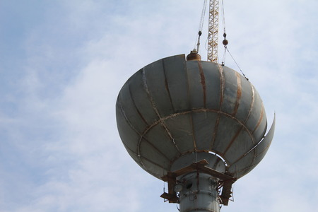 Half way completed the removal of an old rusty water tower 免版税图像