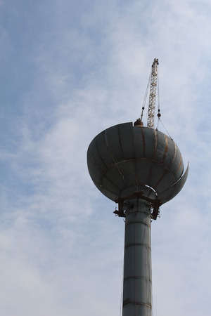 Half way completed the removal of an old rusty water tower Stock Photo