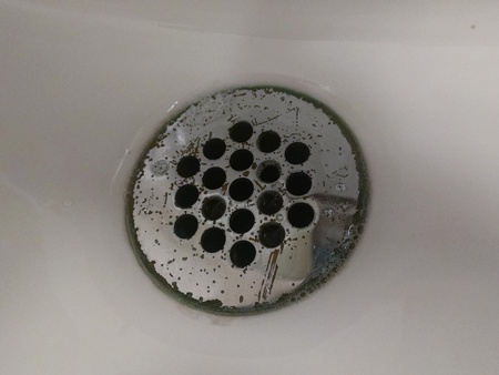 Scratched and worn public restroom sink drain Stock Photo