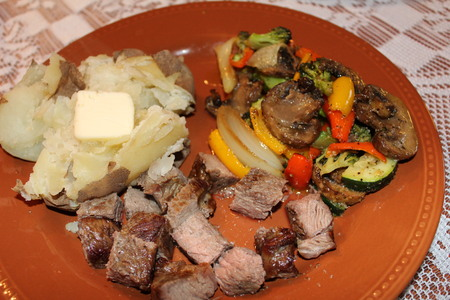 Home made medium rare steak, with baked potato and roasted vegetables served on a porcelain plate. Stock Photo