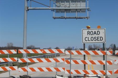 Road Closed barricades for through traffic over bridge.
