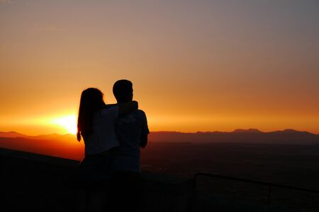 a pair of lovers is watching the sunset