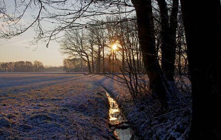 der Sonnenstrahl spiegelt sich wieder im gefrorenen Bach