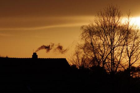 a house with a smoking chimney Standard-Bild