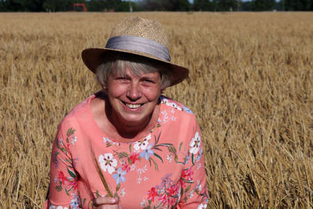woman with straw hat in the middle of a barley field