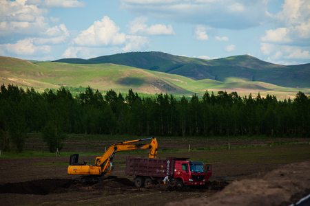 rural area: Excavator and truck in rural area Editorial
