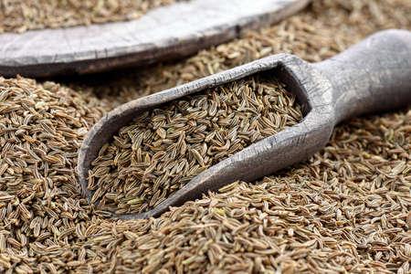 cumin: Cumin seeds with a wooden spoon