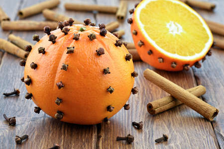 Oranges with cinnamon and cloves on wooden table