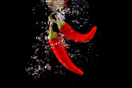 Red chili peppers falling into water at black background