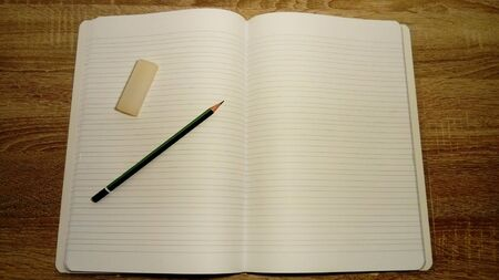 U-turn notebook with white blank sheets. On the left page are a graphic pencil and eraser. Soft light Stock Photo