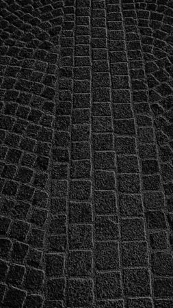 Graphic drawing of paving stones in an ancient square in the old city. Black background with gray pattern.
