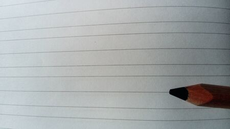 A pencil lies on a striped page. The first time in first class. Student notebook