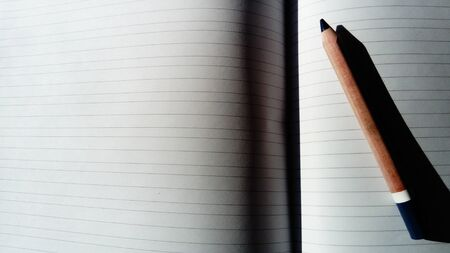 U-turn notebook in a ruler. A pencil lies on a striped page.