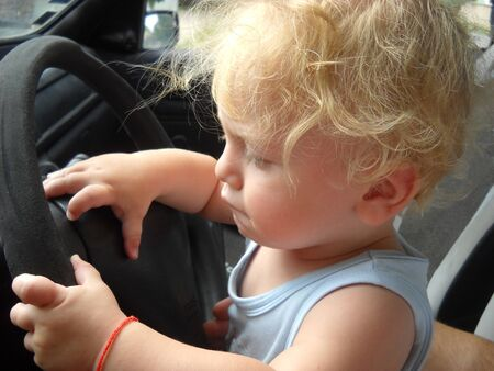A one-year-old boy with magnificent blond hair in a summer T-shirt sits in the car in the driver's seat and pretends that he is the driver of the car. He wants to touch everything Archivio Fotografico
