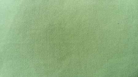Light green woven coarse material, similar to canvas, linen or thick cotton. Thick fabric for upholstery, for bedspreads and covers