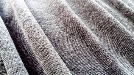 Stretched elastic fabric. Gray material laid in waves. Cloth for sewing covers for chairs, chairs and sofas and for sewing clothes, plush toys, bedspreads and other fabric products.