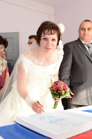 Sremska Mitrovica/Serbia - October 10, 2019: the bride leaned over the table with an open marriage registration book. Woman holding a bouquet of red roses and a ballpoint pen, ready to put a signature.