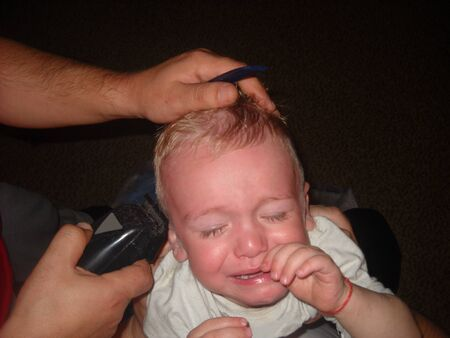 The child cries when his hair is cut on his head. Hairstyle is almost ready. Barber tools, a shaving machine and the hands of a hairdresser in the frame.