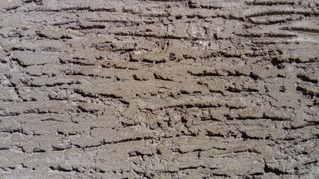Light and shadow.Wall of the house with a self-made plastered facade. The cement mortar is applied to the wall, smeared with a spatula. A decorative pattern was applied on the plaster with an instant Imagens