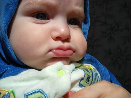 Baby 6 months old on mothers hands. The boy is dressed in a jumpsuit and a blue hood. A child with thick cheeks and a drooping lower lip. Looking to the side, head turning three quarters.