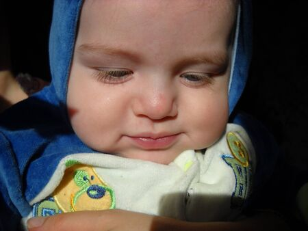 Cute little baby 6 months old in a hood from a blue jumpsuit. The boy looks down and smiles shyly. The natural look of the skin, bright eyelashes are noticeable. High forehead. Stock Photo