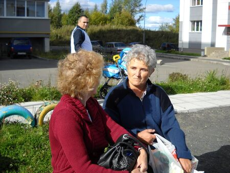 Petrozavodsk / Russia - June 09, 2019: two women who returned from the store with their hacks are sitting on a bench. In the background- a man with a blue stroller and the yard of apartment buildings.
