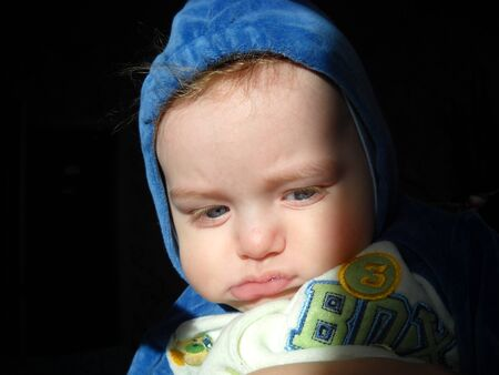 The little child pouted and frowned. Tired, offended or sleepy baby. On the boys head is a hood of blue plush overalls. Natural sunlight from the window.Lower lip with saliva. Red hair underside caps