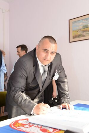 Belgrade / Serbia - October 10, 2019: a man in a gray suit signs. The man is getting married. Before painting in a wedding book, the young man thought about it. The man is looking forward and smiling.