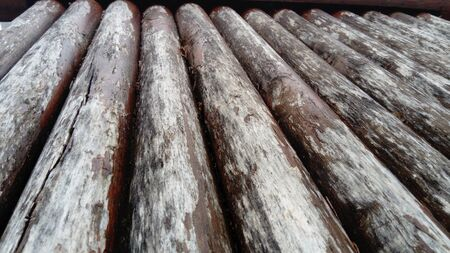 The effect of moisture on wood. A construction log for use in construction without longitudinal sawing. Round timber assortment. Fragment of the construction of rounded wooden logs