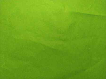 A sheet of thick green paper, slightly wrinkled. Non-uniform lighting.