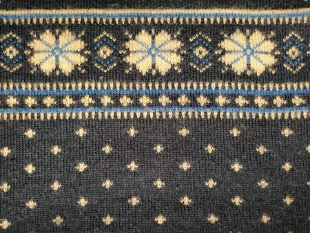 A fragment of an ornament on a knitted polyester or woolen sweater. Winter motives. Blue threads for hand knitting. White thread knitted pattern. Flowers.