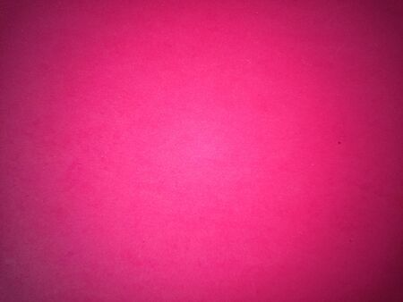Fuchsia color paper background. Dark light vignetting around the edges. Background, greeting card or declaration of love