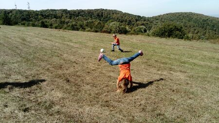 The girl tumbles over her head, leaning on her hands. A boy and a girl with blond hair, dressed in orange t-shirts and classic jeans, play ball in a mountain meadow. Horizon and vegetation