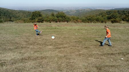 A boy and a girl with blond hair, dressed in orange t-shirts and classic jeans, play ball in a mountain meadow. Early warm autumn. Kids are playing. In the background the horizon and vegetation.