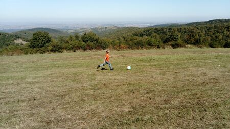 A boy with blond hair, dressed in an orange T-shirt and classic jeans, plays with a ball in a mountain meadow. Early warm autumn. In the background a landscape from the top of the mountain. Banque d'images