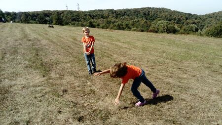 The girl tumbles over her head, leaning on her hands. Moment of motion. A boy and a girl with blond hair, dressed in orange t-shirts and classic jeans, are playing on a mountain meadow