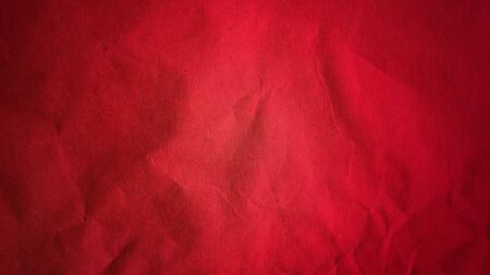 Crumpled red thick paper. Bright beautiful intense blood tint. Texture. Dark vignetting around the edges of the page. Saturated color. Bulge effect.