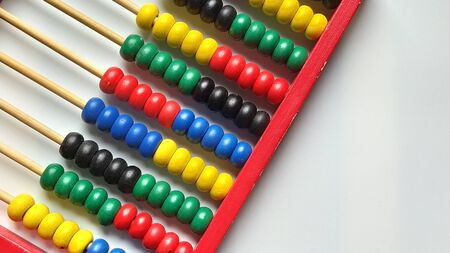 Wooden abacus. Red wooden frame with cross rods. Red, blue, yellow, green, black wooden elements. Math tool on a white background. Close-up. Copy space. Stock fotó