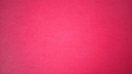 A sheet of bright pink paper with light vignetting around the edges. Intense fuchsia color. Saturated bright paint. Velvet paper texture. Background for greeting card or page. Valentines Day.
