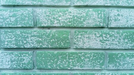 A brick wall. Ceramic brickwork. Brick fence. Neatly and evenly laid brick. Green wall of a building. The brick wall is painted green. Green paint began to wash off in the rain Stockfoto
