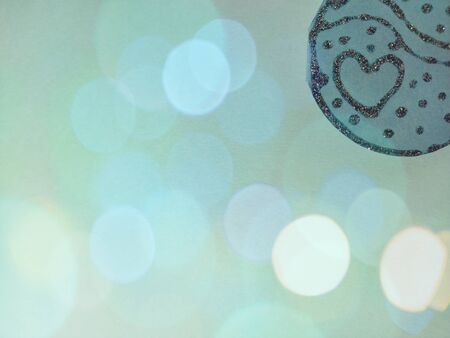 Sparks and bokeh on a blue background. At the top right, a decorative detail of blue paper made of silver with sequins arranged in the form of a heart and smooth rounded lines