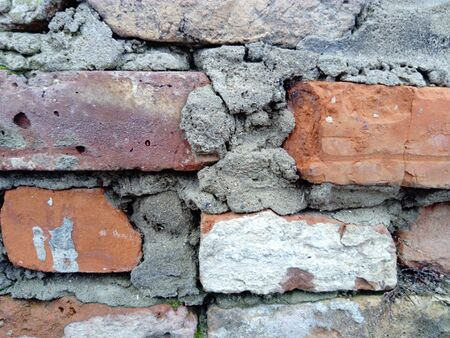 Brick wall. Ceramic masonry or fence. Old, uneven brick, covered in some places with moss and mold. The texture of the stone or mineral. The effect of moisture on brick structures.