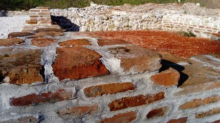 Old roman brick. The restored wall of the building of the Roman conquerors. Warm brown-red shades of uneven bricks. Archaeological site in the city of Sremska Mitrovica, Serbia Stock fotó - 138162672